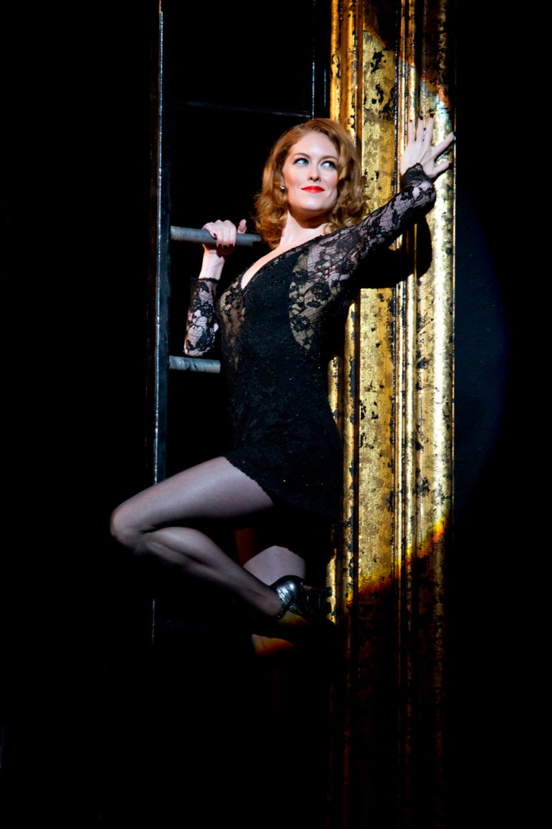 The actress playing Roxie Hart leans against the gold proscenium in a scene from CHICAGO.