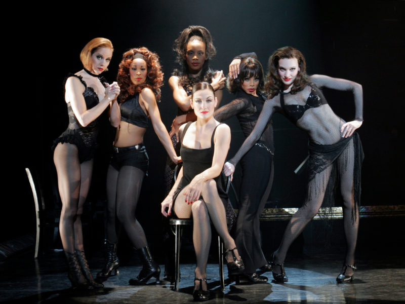 The actress playing Velma Kelly is seated in a chair surrounded by the Merry Murderesses of the Cook County Jail in a scene from Broadway's CHICAGO.